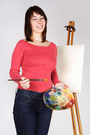 young girl in red shirt standing near easel, holding brush and palette, smiling photo
