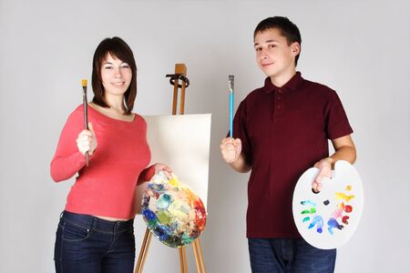 young man and girl standing near easel, holding brushes with palettes and smiling photo