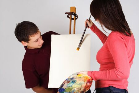 girl holding palette, painting on canvas easel, man looking on picture photo