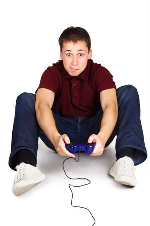 young man sitting on floor, holding joystick and playing console games, exciting face, isolated photo