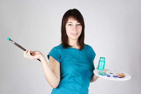 young girl in blue shirt standing and holding brush and palette, smiling photo