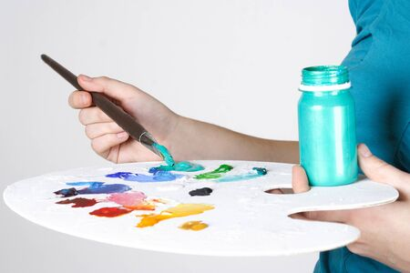 closeup of woman in blue shirt mixing paint on palette photo