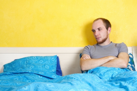 young sad man lying in double bed and looking on empty seat, bright interior photo