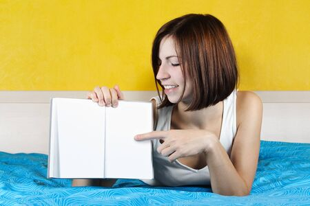 young woman in white undergarment lying in bed on belly and pointing at book, bright interior photo