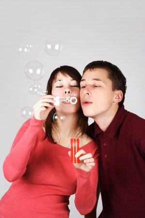 young brunette man and woman in red shirts blowing out soap bubbles photo