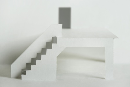 paper cutout composition with white elements of building, terrace with stairs and door photo