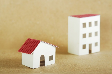paper models of village and city dwelling houses with red roofs, brown background photo