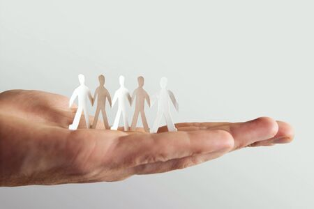 human holding little paper cutout people, team and friendship concept