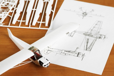 plane table: kit for assembling white plastic airplane model with scheme