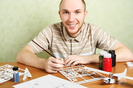 man assembling plastic airplane model and painting pieces, smiling, looking at camera photo
