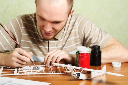 man assembling plastic airplane model and painting pieces photo