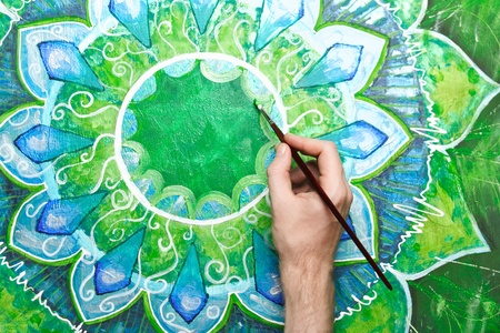 anahata: man painting bright green picture with circle pattern, mandala of anahata chakra Stock Photo