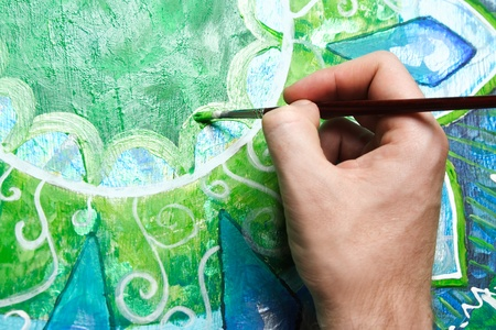 anahata: closeup of man painting green picture with circle pattern, mandala of anahata chakra Stock Photo