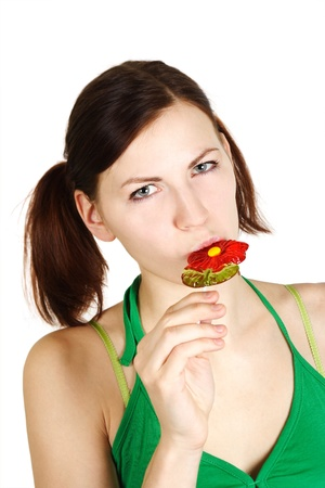young girl in green shirt eating flower lollipop and looking at camera, isolated photo