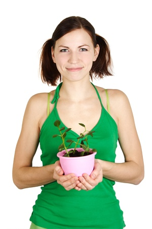 young girl in green shirt holding potted plant and smiling, isolated photo