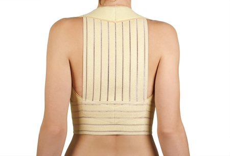 remedial: woman in remedial corset for posture correction, view from back, isolated
