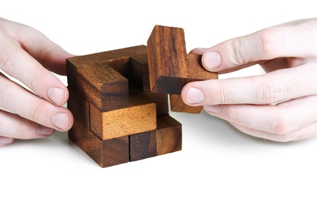 closeup of mans hands assembling wooden cube puzzle, isolated photo