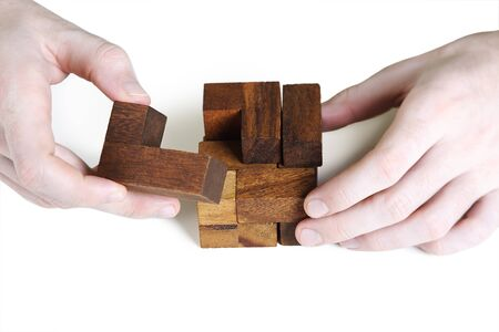 wooden figure: closeup of mans hands assembling wooden cube puzzle, isolated