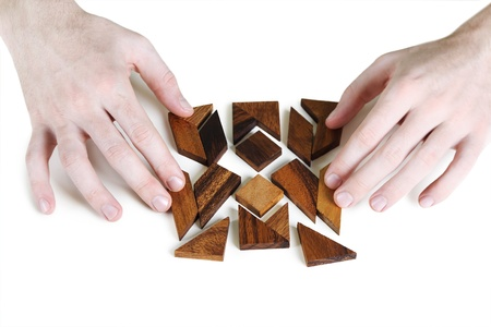 closeup of mans hands assembling wooden square puzzle, isolated photo