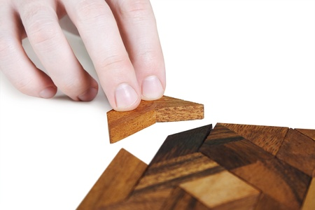 closeup of human hand assembling wooden square puzzle, isolated photo