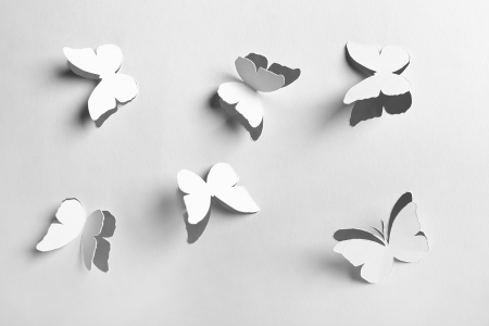 cut paper: white abstract paper cutout butterflyes Stock Photo