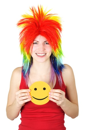 young beauty woman in multicolored clown wig smiling and holding cardboard smile, isolated photo
