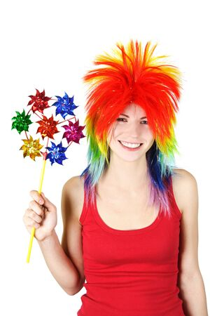 young beauty woman in multicolored clown wig smiling and holding pinwheel, isolated photo