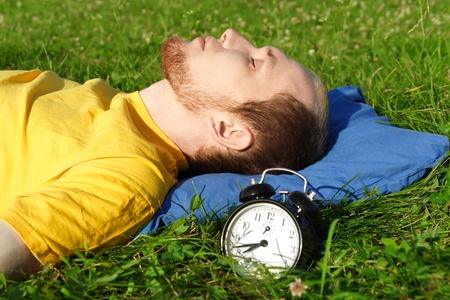 man white breard in yellow shirt sleeping on summer meadow near clock, lying on back, rest concept photo