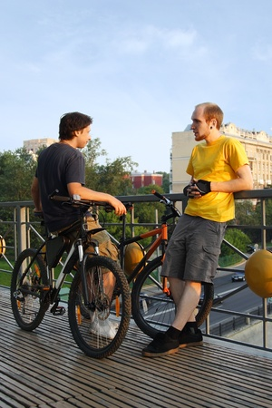 two young men in sport clothes standing on bridge near bicycles and talking photo