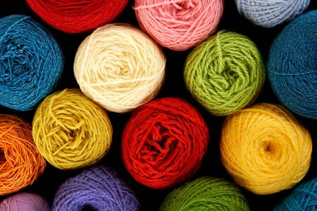crochet: many multicolored clews, view from above, isolated on black