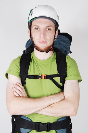 mountain tourist in helmet and with big backpack standing with crossed hands photo