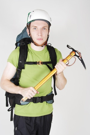 mountain tourist in helmet and with big backpack standing and holding pick Stock Photo - 9976700