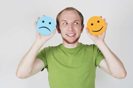 young man in green shirt holding emotion smile symbols Stock Photo - 9976846