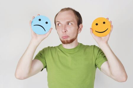 young man in green shirt holding emotion smile symbols photo
