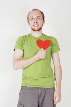 young man in green shirt holding valentine heart card Stock Photo - 9976830