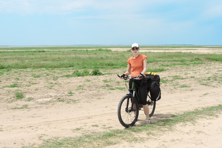 bicycle tourist girl standing on road, blue sky and horizon photo