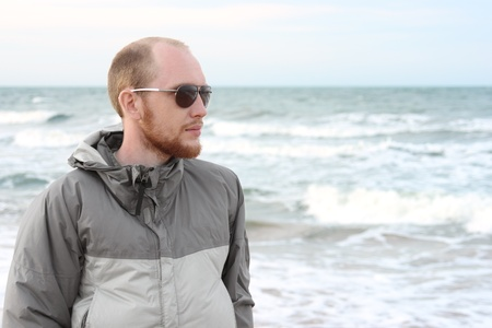 serious guy: portrait of man with beard in sunglasses near sea