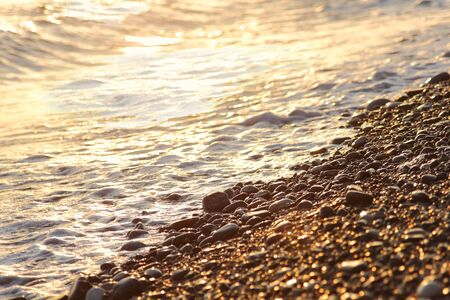 shingle beach: closeup of shingle beach and sea waves with sunlight Stock Photo