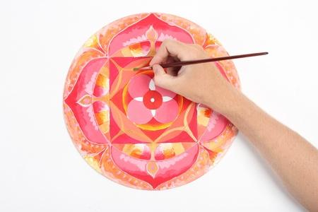 hand schilderen: man de hand schilderen abstract beeld met rode cirkel patroon, mandala van Muladhara chakra