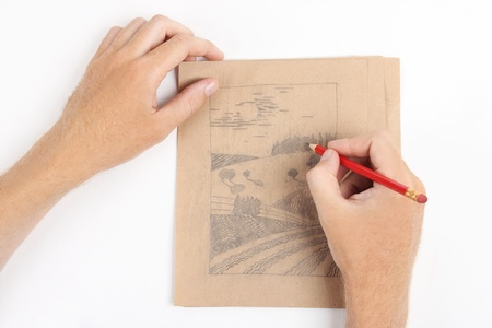 man hands draw picture with landscape on brown paper photo