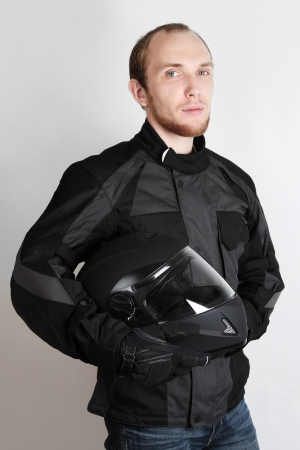young motorcyclist man holding helmet in studio photo