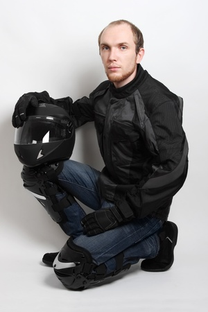 young motorcyclist man sitting and holding helmet in studio photo