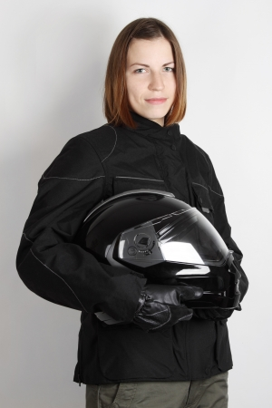 young motorcyclist woman holding helmet in studio photo