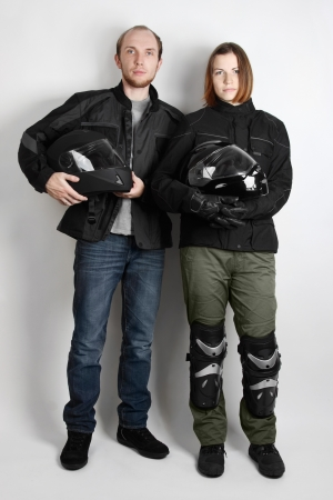 young motorcyclists man and woman holding helmets in studio photo