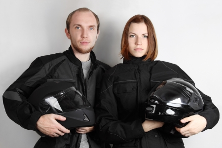young motorcyclists man and woman holding helmets in studio Stock Photo - 14162274