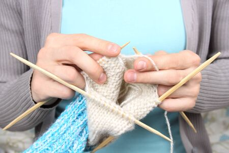woman knitting blue socks closeup photo