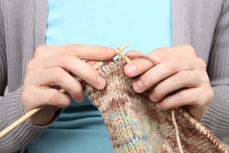 woman knitting brown threads closeup