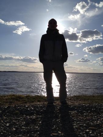 man: Man silhouette near river