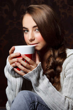 Beautiful young girl drinking hot chocolate photo