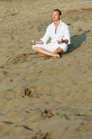 Beautiful man meditating on river beach photo